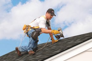 Worker repairing hail damage on shingle home in Staunton, Virginia - Staunton Roofing